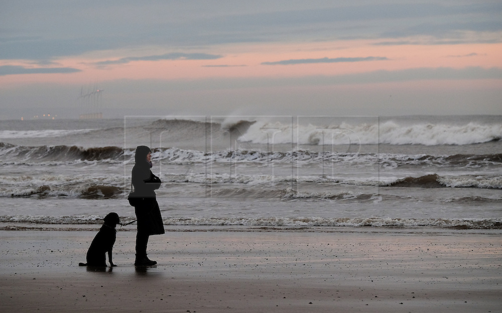 © Licensed to London News Pictures. 08/01/16<br /> Saltburn, UK. <br /> <br /> A woman stands with her dog and looks at the surf as day breaks at Saltburn beach. <br /> <br /> Photo credit : Ian Forsyth/LNP