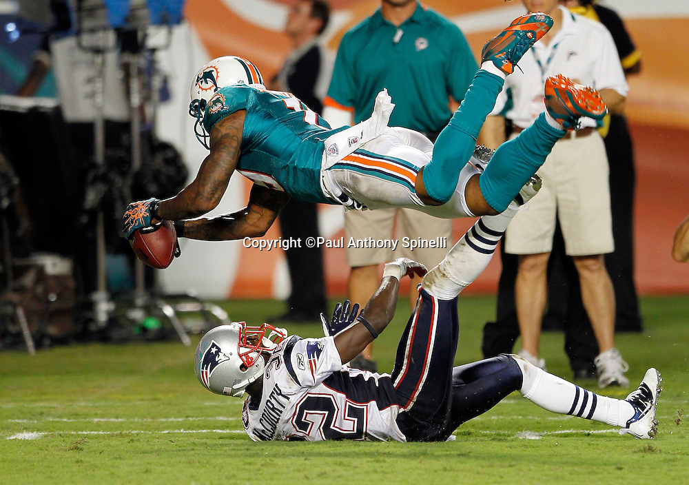 Miami Dolphins wide receiver Brandon Marshall (19) dives while catching a third quarter pass inside the five yard line while covered by New England Patriots defensive back Devin McCourty (32) during the NFL week 1 football game against the New England Patriots on Monday, September 12, 2011 in Miami Gardens, Florida. The Patriots won the game 38-24. ©Paul Anthony Spinelli