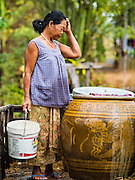 20 JANUARY 2016 - SI LIAM, BURI RAM, THAILAND: A woman checks the water she traveled more than a mile to find. Her rice crop failed and she can't afford to buy water so everyday she goes out looking for water. She sometimes sells what water she has left over. The drought gripping Thailand was not broken during the rainy season. Because of the Pacific El Nino weather pattern, the rainy season was lighter than usual and many communities in Thailand, especially in northeastern and central Thailand, are still in drought like conditions. Some communities, like Si Liam, in Buri Ram, are running out of water for domestic consumption and residents are traveling miles every day to get water or they buy to from water trucks that occasionally come to the community. The Thai government has told farmers that can't plant a second rice crop (Thai farmers usually get two rice crops a year from their paddies). The government is also considering diverting water from the Mekong and Salaween Rivers, on Thailand's borders to meet domestic needs but Thailand's downstream neighbors object to that because it could leave them short of water.        PHOTO BY JACK KURTZ