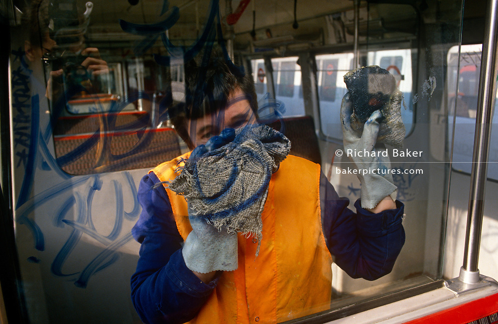 A London Underground employee wipes hard to remove the tagging left behind by permanent marker pens on London Transport property in 1989.