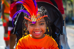 Resplendent in her carnival head dress, a little girl smiles for the camera on Ladbroke Grove as day one, Children's Day, of the Notting Hill Carnival gets underway in London. London, August 25 2019.