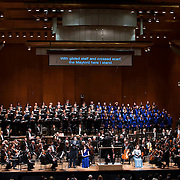 """November 21, 2013 - New York, NY :  Conductor Alan Gilbert, on podium, leads the New York Philharmonic, the New York Choral Artists, and the Brooklyn Youth Chorus, along with vocal soloists, foreground from center left, tenor Dominic Armstrong (standing), soprano Kate Royal (seated in violet dress), and mezzo-soprano Sasha Cooke (seated in sequined dress) in Bejamin Britten's """"Spring Symphony, Op. 44 (1948-49)"""" with the New York Philharmonic at Avery Fisher Hall at Lincoln Center on Thursday night. Armstrong made his NY Phil debut as a last-minute substitution for tenor Paul Appleby, who withdrew due to illness. CREDIT: Karsten Moran for The New York Times"""
