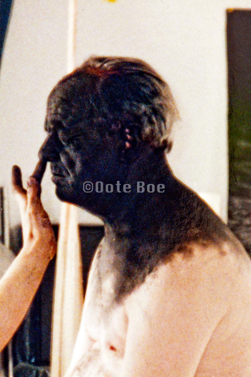 black face being painted on a caucasian senior man