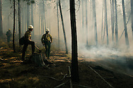 USFS firefighters Dirk Stevens, left, and Sean Wishart, right, monitor a border of a controlled burn near Pringle Falls five miles west of La Pine, Ore. Thursday afternoon. The Bulletin/Rob Ker