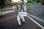 "Dec. 2, 2009 -- PHOENIX, AZ: LIZ HOURICAN and others opposed to the US troop increase in Afghanistan pit on a skit in an intersection in Phoenix Wednesday. They ran through the intersection having a ""tug of war"" with warfare vs. health care. About 50 people from across the Phoenix metropolitan area attended the protest and vigil against the troop increase President Barack Obama announced on Dec. 1. Photo by Jack Kurtz"