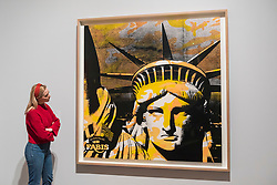 "© Licensed to London News Pictures. 10/03/2020. LONDON, UK. A staff member views ""Statue of Liberty (Fabis)"", 1986, by Andy Warhol. Preview of ""Andy Warhol"", a retrospective of over 100 works by one of the most recognisable artists of the late 20th century.  The exhibition runs 12 March to 6 September 2020 at Tate Modern.  Photo credit: Stephen Chung/LNP"