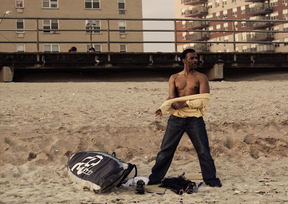 An African American man puts his shirt on after a surf session at Rockaway Beach, Queens, NY.