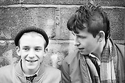 Neville and friend in School Uniform in front of a brick wall, 1980s.