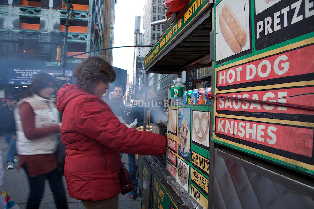 person buying food at a hot dog stand New York City