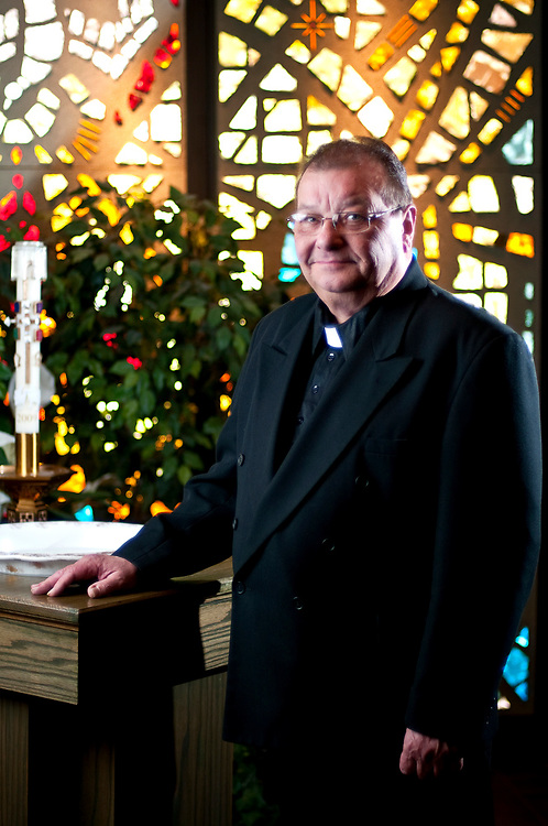 Father Ronald J. Lejeune stands in front of a stained glass window at the Holy Trinity Catholic Church in Bucyrus on Thursday. Beginning July 1, 2010 Father Lejeune will tend the flocks of both the Holy Trinity and St. Joseph's Catholic Church, in Galion.