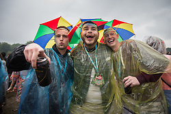© Licensed to London News Pictures . 07/06/2014 . Heaton Park , Manchester , UK . Men dancing with cans of cider wearing umbrella hats . The Parklife music festival in Heaton Park Manchester following heavy overnight rain . Photo credit : Joel Goodman/LNP
