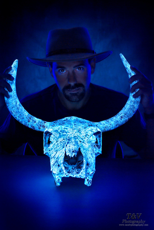 A man wearing a cowboy hat holds the form of a glowing cow skull.Black light