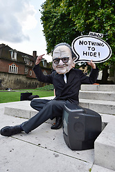 © Licensed to London News Pictures. 12/09/2017. London, UK. A man sits outside the Houses of Parliament wearing a papier mache head mask of Rupert Murdoch as Karen Bradley, Culture Secretary, announces that she will refer 21st Century Fox's GBP11.67bn bid to buy Sky to competition regulators on the grounds of media plurality and broadcasting standards. Photo credit : Stephen Chung/LNP
