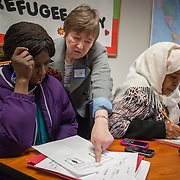 "Atlanta, Georgia/Central Africa Republic Refugee/Nestorine Lakas, 27, (purple jacket) gets help from volunteer ESL teacher Jan Sanders, during a First Things First class at the IRC in Atlanta. Nestorine arrived in the U.S. in 2010 with her two young children from the Central African Republic. Eric, 7, who has cerebral palsy, requires a wheelchair and specialized healthcare. At the IRC in Atlanta, Nestorine is part of the Temporary Assistance for Needy Families (TANF) program where she is learning English, job skills and basic computer literacy so she can support her family as a single mom and learn how to manage her son's health needs. Unfortunately the father of Nestorine's children was not able to come to the U.S. with her, so she cares for her children and dreams of reuniting with him someday. Nestorine believes what makes her successful is ?working hard and overcoming challenges?. ""There was a war in my country and I fled to Cameroon. I was pregnant with my older son and gave birth along the way. When I fled I was alone. When I got to the camp I found my husbands name on a sign at the camp and we were reunited. My daughter Carol (3) was born in Cameroon."" Because of her son's disability Nestorine got a humanitarian visa with the help of UNHCR. ""I am very happy to be here because they helped me a lot with my child. If I had stayed in CAR there isn't the healthcare that I have here. I am very thankful. The reason my child is still alive because I came as a refugee. Maybe the child would not have had any hope to walk. I hope one day he might walk.""."