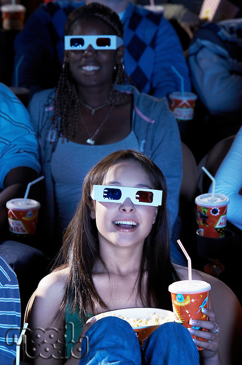 People wearing 3-d glasses watching 3-D movie in theatre