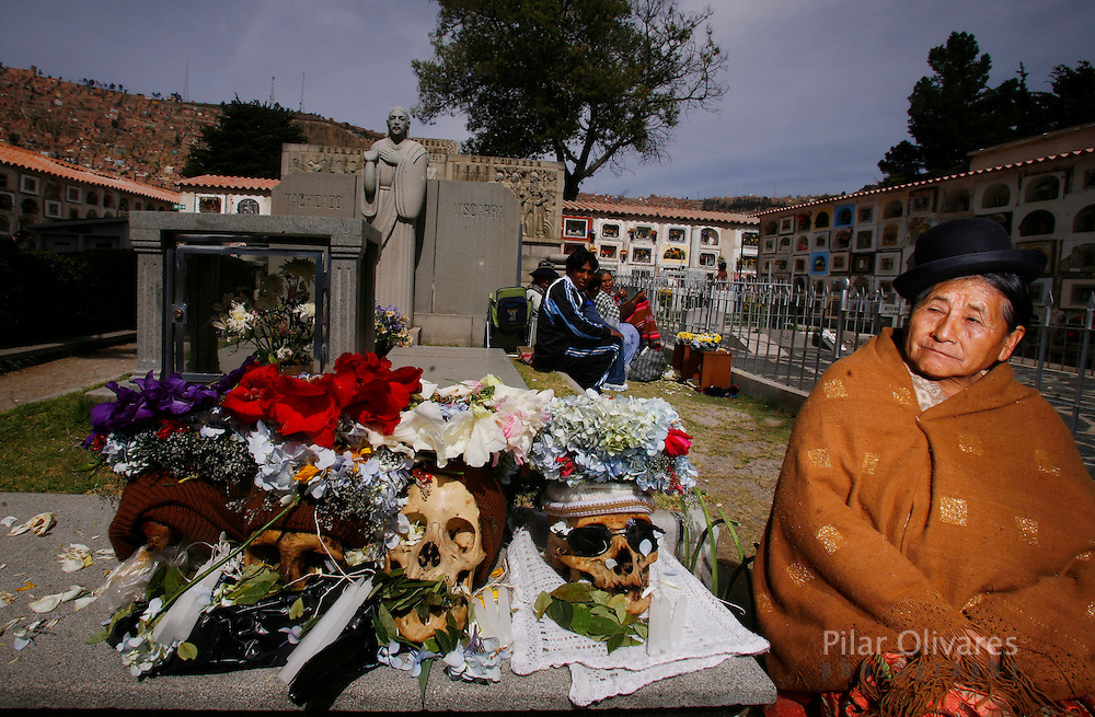 A woman sits next to skulls at the General Cemetery on the Day of Skulls in La Paz November 8, 2009. Bolivians who keep close relatives' skulls at home as a macabre talisman flock to the cemetery chapel once a year to have the craniums blessed and to bring themselves good luck in the future.
