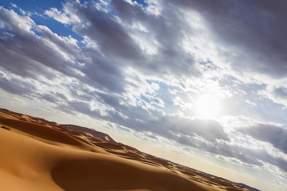 Sahara desert sand dunes with cloudy blue sky and sun, Erg Chebbi, Merzouga. Morocco.