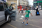 A young boy plays football at Hackney Central while his father makes calls inside his van, his legs propped up on the door.