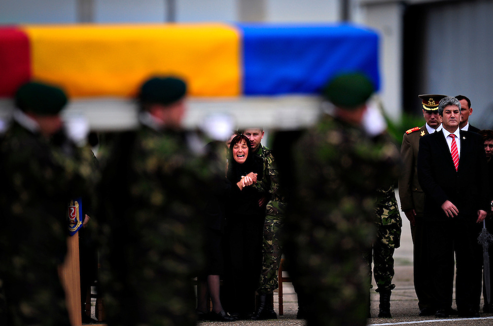 Coffins with the bodies of Lieutenants Dan Ciobotaru and Paul Caracuda, who died during a patrol mission in Afghanistan, are brought in Romania, during a military ceremony, attended by their families and by the Romanian Defense secretary of State, Gabriel Oprea (right).