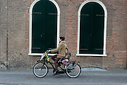 Een vrouw fietst met haar kind achterop over het Janskerkhof in Utrecht.<br /> <br /> A woman is cycling with her child at the back of her bike near Janskerkhof in Utrecht.