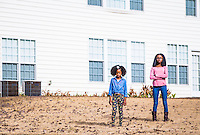 Two little girls in backyard of white house