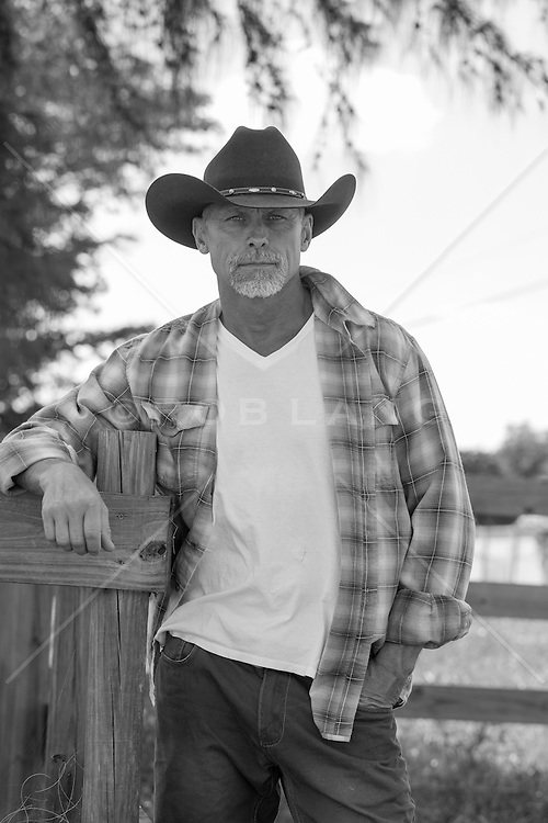 good looking older cowboy leaning on a fence