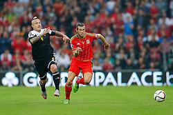 Gareth Bale of Wales (Real Madrid) gets away from Radja Nainggolan of Belgium (Roma) - Photo mandatory by-line: Rogan Thomson/JMP - 07966 386802 - 12/06/2015 - SPORT - FOOTBALL - Cardiff, Wales - Cardiff City Stadium - Wales v Belgium - EURO 2016 Qualifier.