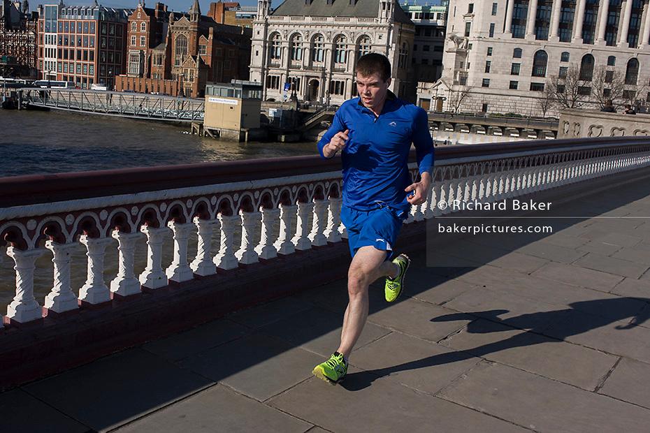 Male lunchtime jogger runs over Blackfriars Bridge.
