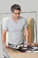 Mature male fashion designer looking at cloth swatches