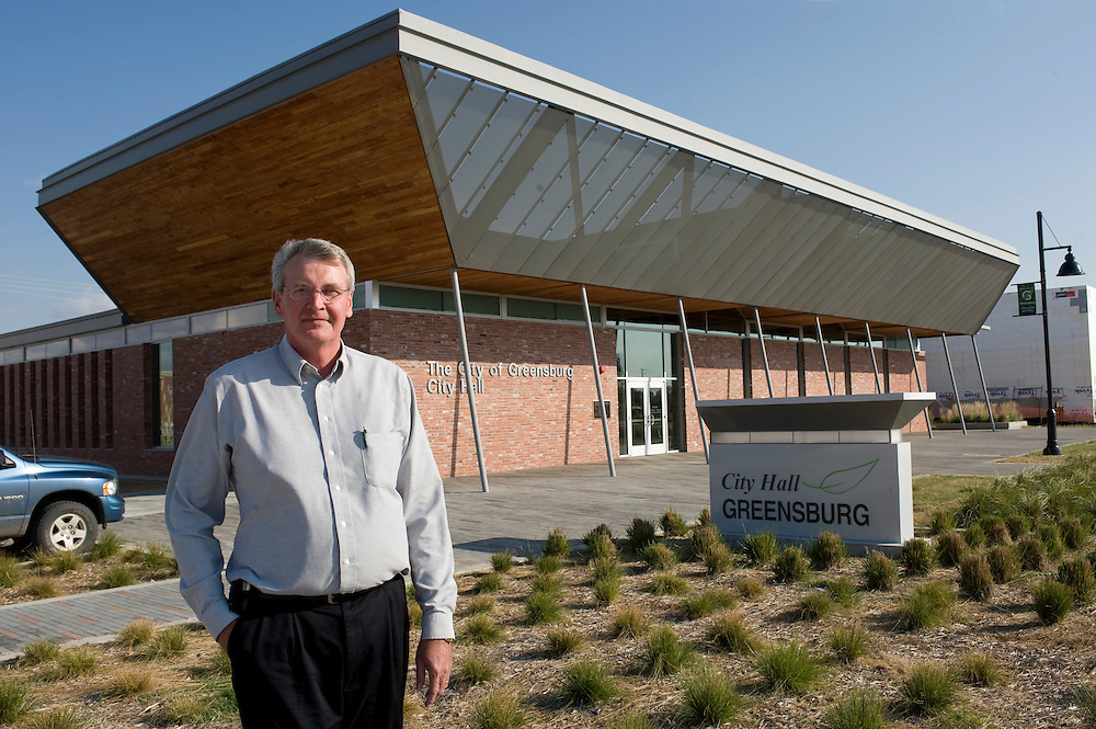 """Greensburg, Kansas, USA..Buergermeister Bob Dixon vor dem Stadthaus..Mayor Bob Dixon in front of City Hall. .Greensburg City Hall, designed by Kansas City-based BNIM architects to be a LEED Platinum building, at Wisconsin Avenue and Main Street, was completed in October 2009. It was the first new construction LEED Platinum city hall building in America, and includes solar panels and geothermal technology. It has been built out of reclaimed brick from the Greensburg power plant (destroyed by the tornado), and recycled wood and materials. It has a green roof with vegetation growing on the east end of the roof...""""Greensburg: Better, Stronger, Greener!"""".On May 4, 2007, an EF5 tornado cut a 1.7-mile path of destruction through Greensburg, Kansas. Winds reaching speeds of 205 miles per hour uprooted trees, demolished homes and leveled the town. Eleven people died and 95% of the buildings were destroyed beyond repair. Residents have since worked furiously to rebuild it in a way that is both economically and environmentally sustainable and to meet the highest environmental standards. Greensburg, whose population has dropped from about 1400 to 800 following the storm and is now growing again, is currently the greenest town in America and the first in the United States to pass a resolution to certify that all city-owned buildings earn LEED Platinum accreditation, the highest level of the LEED rating system...Foto © Stefan Falke"""
