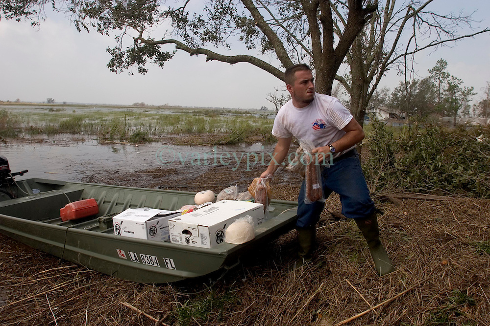 25 Sept, 2005. Carlyss, Louisiana.  Hurricane Rita aftermath. <br />  Local cajun man Chase Reider takes his boat to unload meat from a family convenience store to a family home where a generator powering freezers and refrigerators will stop the meat from spoiling.<br /> Photo; &copy;Charlie Varley/varleypix.com