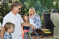 Family of four barbecuing