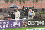 Rain Stops Play - Spectators walk around the ground with umbrellas up as the heavy rain continues to fall during the Specsavers County Champ Div 1 match between Somerset County Cricket Club and Essex County Cricket Club at the Cooper Associates County Ground, Taunton, United Kingdom on 23 September 2019.