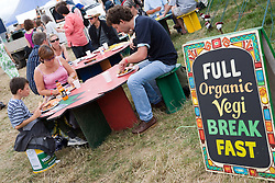 People eating at an outdoor organic vegetarian cafe at the WOMAD (World of Music; Arts and Dance) Festival in reading; 2005,