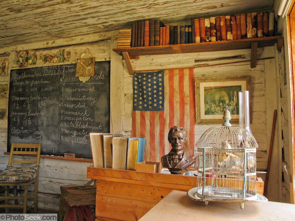 "Montana's oldest standing public school, used in the town of Twin Bridges from 1867-1873, is now preserved at Nevada City, Montana, USA. The wooden classroom contains a desk, old books, chalkboard, an American flag with 48 stars, a bust of President Lincoln, a bird cage, and chairs. Nevada City was a booming placer gold mining camp from 1863-1876, but quickly declined into a virtual ghost town. This fascinating town inspires you to imagination what life must have been like in early Montana when gold was discovered at nearby Alder Gulch. More than 90 buildings from across Montana have been gathered for preservation at Nevada City, mostly owned by the people of the State of Montana, and managed by the Montana Heritage Commission. In 2001, the excellent PBS television series ""Frontier House"" used one of the buildings and its furnishings to train families in re-creating pioneer life. A miner's court trial and hanging of George Ives in the main street of Nevada City was the catalyst for forming the Vigilantes, a group of citizens famous for taking justice into their own hands in 1863-1864. Directions: go 27 miles southeast of Twin Bridges, Montana on Highway 287."