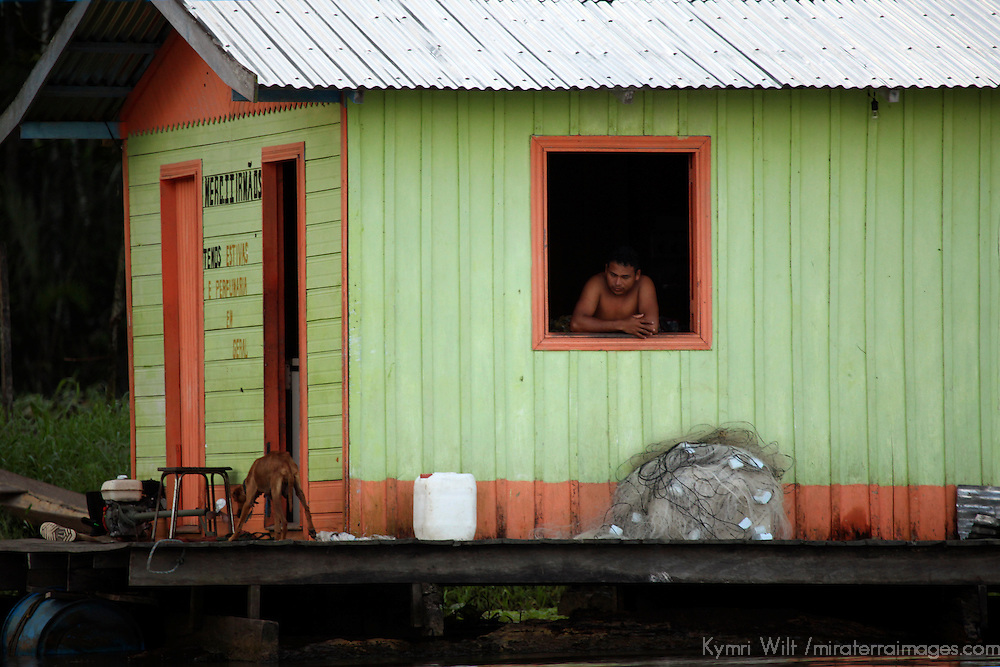 South America, Brazil, Amazon.  A man and a dog on the Amazon.