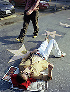 Man walking past another man laying down on Hollywood walk of fame with his head resting on red sweater and newspapers.