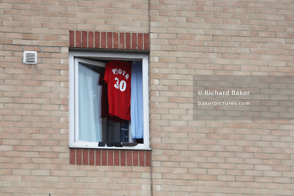A Polish football shirt belonging to Piotr dries on a hangar in an open Ibis hotel window in industrial West Thurrock