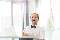 Cheerful businessman sitting at desk in creative office