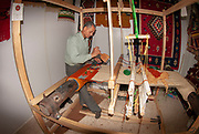 Man hand weaves a woollen rug on a loom at a Handicraft shop in Madaba Jordan