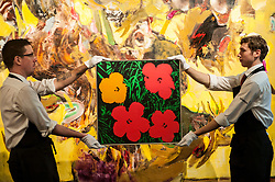 "© Licensed to London News Pictures. 28/01/2016. London, UK.   ""Flowers"" by Andy Warhol (est. £1.3-1.8m) is shown in front of ""The Sunflowers"" by Adrien Ghenie (est. £0.4-0.6m), at Sotheby's preview of its upcoming Impressionist, Modern & Surrealist art sale on 3 February featuring works by some of the most important artists of the 20th century.  The combined total of the evening sale is expected to exceed £100m. Photo credit : Stephen Chung/LNP"
