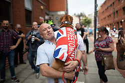 """© Licensed to London News Pictures. 01/06/2018. Leeds, UK. A man carrying a dog with a Union Jack flag and the words """" FREE TOMMY """" . Supporters of EDL founder Tommy Robinson ( real name Stephen Yaxley-Lennon ) demonstrate in Leeds after Robinson was convicted of Contempt of Court . Robinson was already serving a suspended sentence for Contempt of Court over a similar incident , when he was convicted on Friday 25th May 2018 . Reporting restrictions , since lifted , initially prevented coverage of Robinson's arrest and incarceration . Photo credit: Joel Goodman/LNP"""