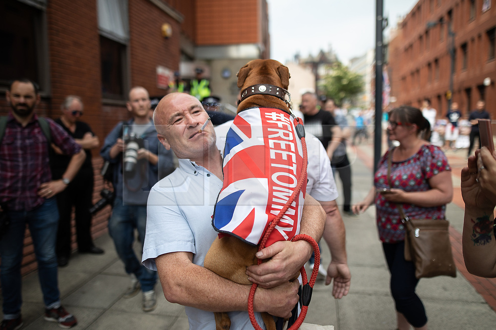 "© Licensed to London News Pictures. 01/06/2018. Leeds, UK. A man carrying a dog with a Union Jack flag and the words "" FREE TOMMY "" . Supporters of EDL founder Tommy Robinson ( real name Stephen Yaxley-Lennon ) demonstrate in Leeds after Robinson was convicted of Contempt of Court . Robinson was already serving a suspended sentence for Contempt of Court over a similar incident , when he was convicted on Friday 25th May 2018 . Reporting restrictions , since lifted , initially prevented coverage of Robinson's arrest and incarceration . Photo credit: Joel Goodman/LNP"