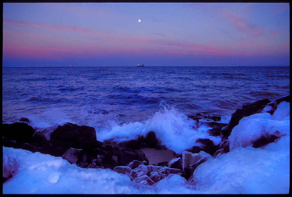 THE FREIGHTER ALGOSTEEL ENTERS MARQUETTE'S UPPER HARBOR UNDER A FULL MOON AT DUSK AS LAKE SUPERIOR WAVES CRASH ON THE SHORE IN MARQUETTE MICHIGAN.