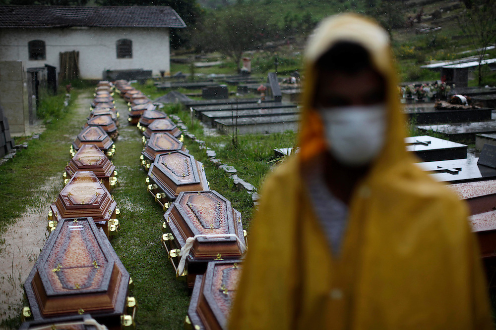 Wearing face masks to prevent infections, a man stand next to coffins containing bodies of landslides victim at a cemetery in Nova Friburgo, Brazil, Saturday, Jan. 15, 2011. <br /> <br /> A series of flash floods and mudslides struck several cities in Rio de Janeiro State, destroying houses, roads and more. More than 900 people are reported to have been killed and over 300 remain missing in this, Brazil&rsquo;s worst-ever natural disaster.