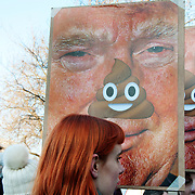 London UK. January 21st 2017.An estimated 100,000 protesters took part in a Women's March from the US Embassy in Grosvenor Square to Trafalgar Square as part of an international campaign on the first full day of Donald Trump's Presidency of the United States. A red haired woman holds a caricatured photo of Donald Trump with nose covered by excrement