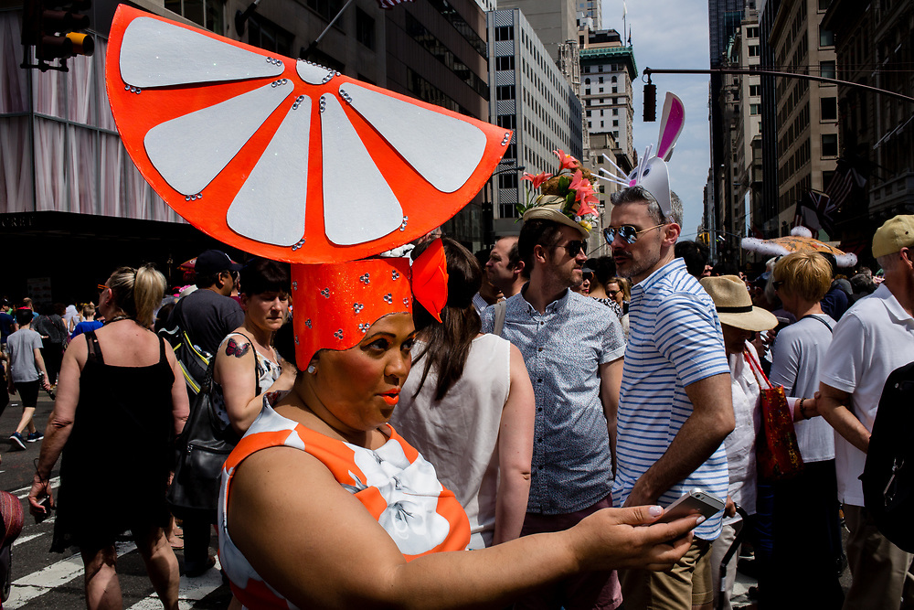 New York, NY - April 16, 2017. A woman with a hat shaped like a giant slice of orange fruit at New York's annual Easter Bonnet Parade and Festival on Fifth Avenue.