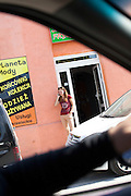 Woman taking a cell phone break outside of a shop. Rawa Mazowiecka Central Poland