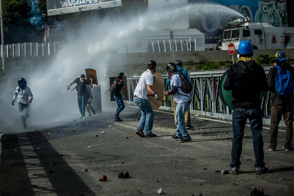 CARACAS, VENEZUELA - MAY 24, 2017:  Anti-government protesters hurl stones and molotov cocktails during clashes with National Guard soldiers who responded by using a water cannon against them, and heavily tear gassing and firing rubber bullets and buckshot at them. The streets of Caracas and other cities across Venezuela have been filled with tens of thousands of demonstrators for nearly 100 days of massive protests, held since April 1st. Protesters are enraged at the government for becoming an increasingly repressive, authoritarian regime that has delayed elections, used armed government loyalist to threaten dissidents, called for the Constitution to be re-written to favor them, jailed and tortured protesters and members of the political opposition, and whose corruption and failed economic policy has caused the current economic crisis that has led to widespread food and medicine shortages across the country.  Independent local media report nearly 100 people have been killed during protests and protest-related riots and looting.  The government currently only officially reports 75 deaths.  Over 2,000 people have been injured, and over 3,000 protesters have been detained by authorities.  PHOTO: Meridith Kohut