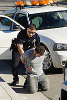 Police Officer Arresting Young Man